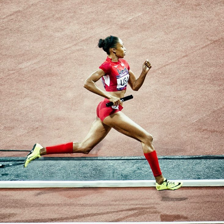 Allyson Felix running on a track. She is shown mid-stride, wearing a red crop top, shorts, and socks, and neon green running shoes.