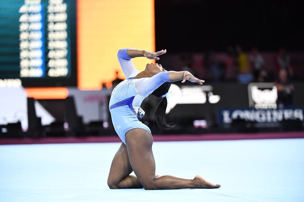 Biles performing a floor routine. She is wearing a blue leotard, and is down on her knees, with her chest and head lifted up to the sky.