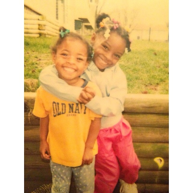 Biles and her sister when they were very young. Biles is hugging her sister and they both have huge grins on their faces.
