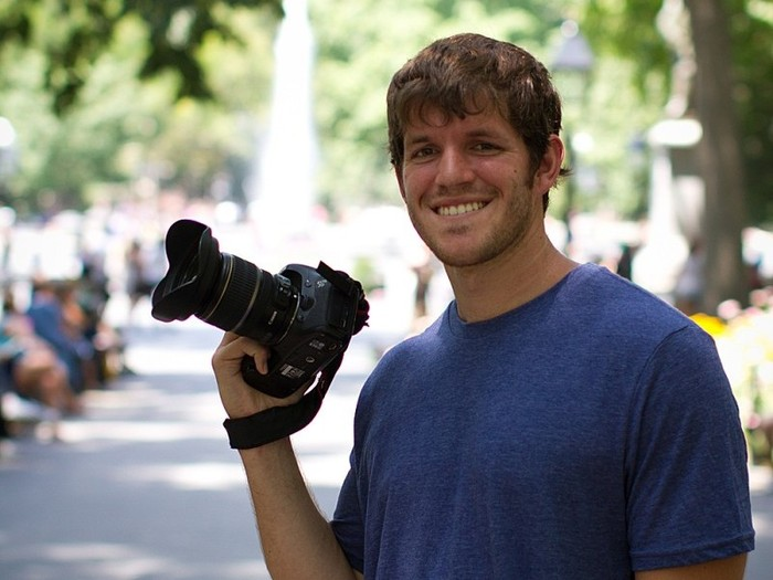Brandon Stanton smiling, with camera in hand.