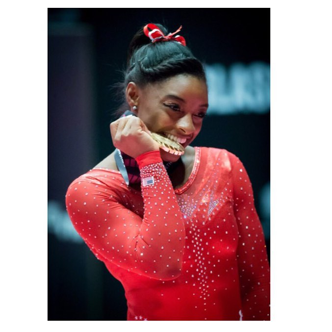 Biles biting on her gold medal in 2015, when she became the world all-around champion for the third year in a row. She is wearing a red leotard with a red bow in her hair.