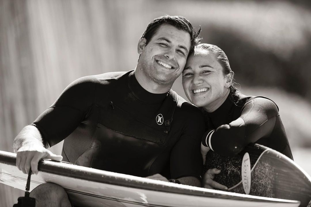 Carissa Moore (right) and her husband, Luke left), holding their surfboards and smiling for the camera.