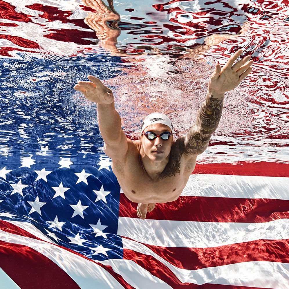 Caeleb Dressel swimming toward the camera, with a huge American flag in the background (underwater).