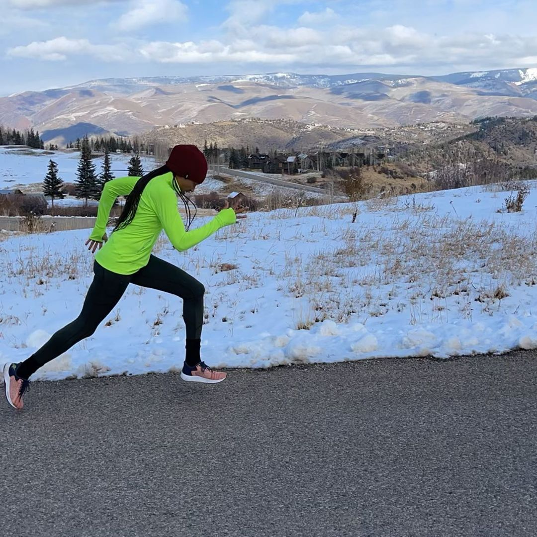 Felix running on a road in the mountains. Snow is shown beside her (on the side of the road), and she is wearing a neon green jacket and black leggings.