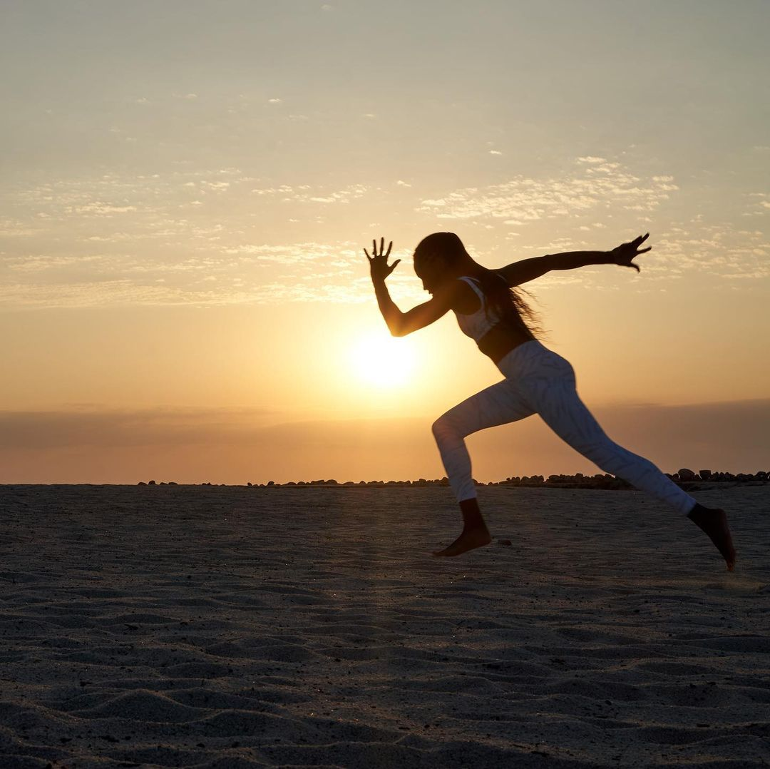 Felix running on the beach, mid-stride, with the sunset behind her.