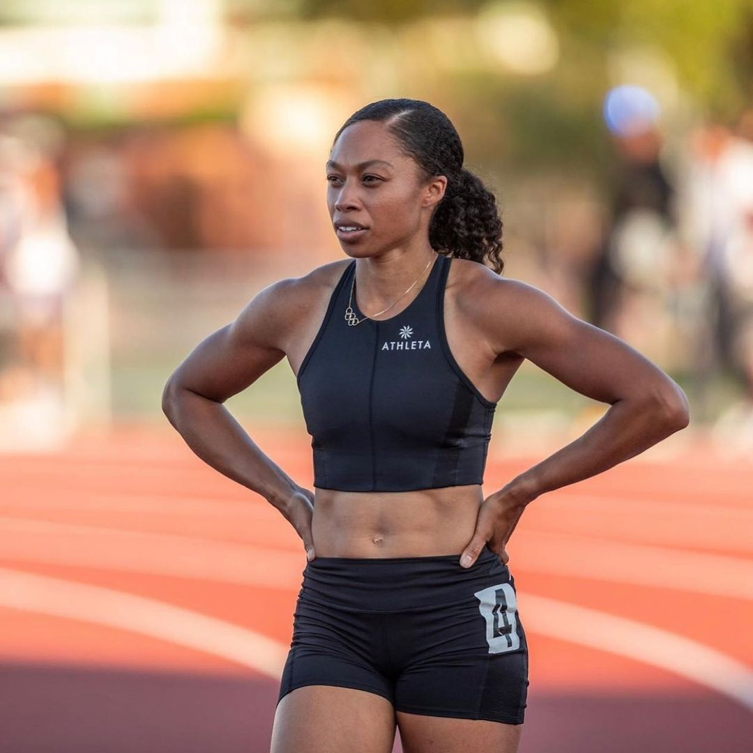 Felix on the track, taking a pause, with her hands on her hips. She is shown wearing a black crop top and black shorts.