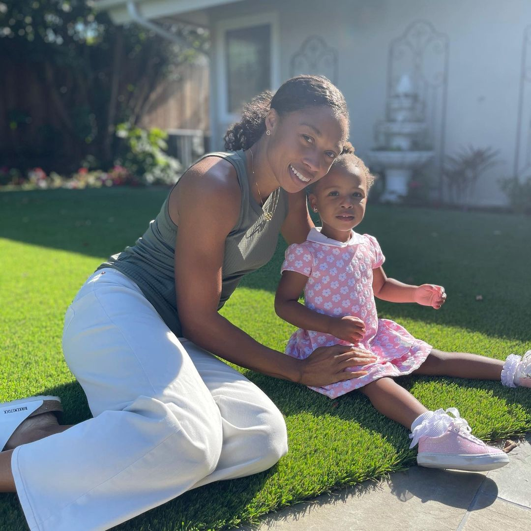 Felix smiles for the camera while hugging her daughter, Camryn. They are shown sitting on grass outside, in front of a house.