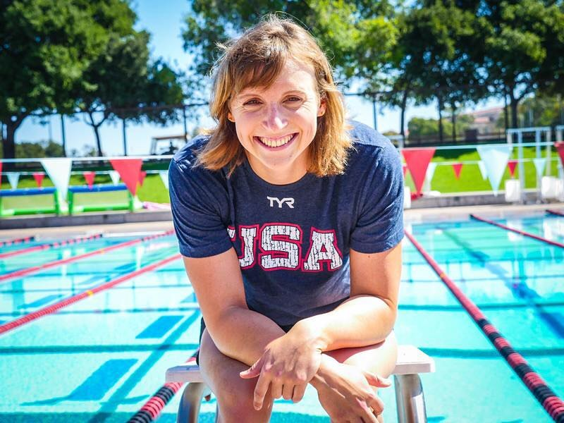 """Katie Ledecky sitting in front of a pool, smiling, with her """"Team USA"""" shirt on."""