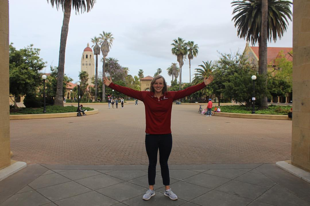 Katie Ledecky with her arms outstretched, standing on Stanford University's campus.