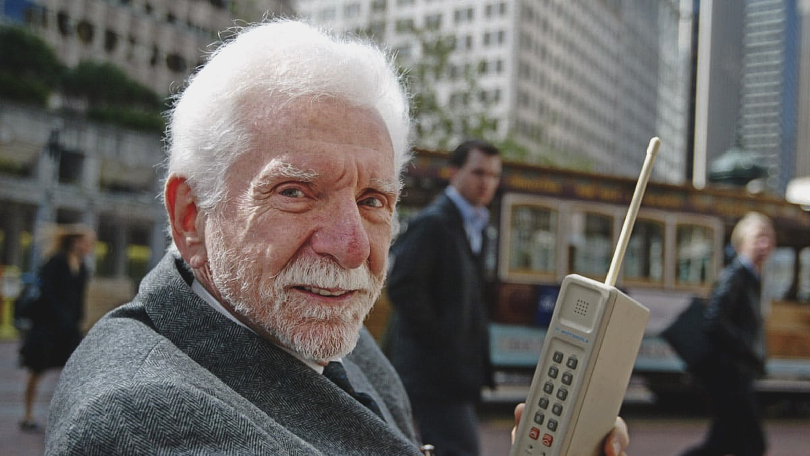Marty Cooper with the first cell phone, looking at the camera