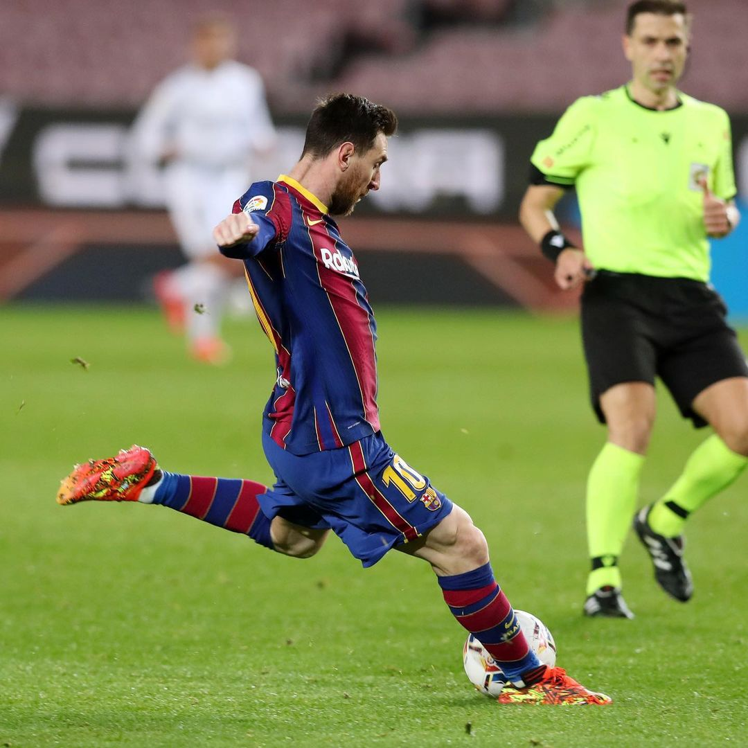 Lionel Messi in action on the soccer field, kicking a soccer ball.