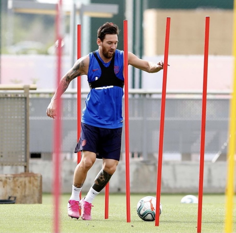 Messi in training, kicking a soccer ball between poles.