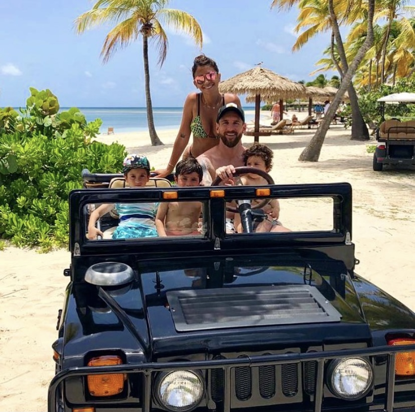 Messi with his wife and three sons, sitting in a jeep on a beach.