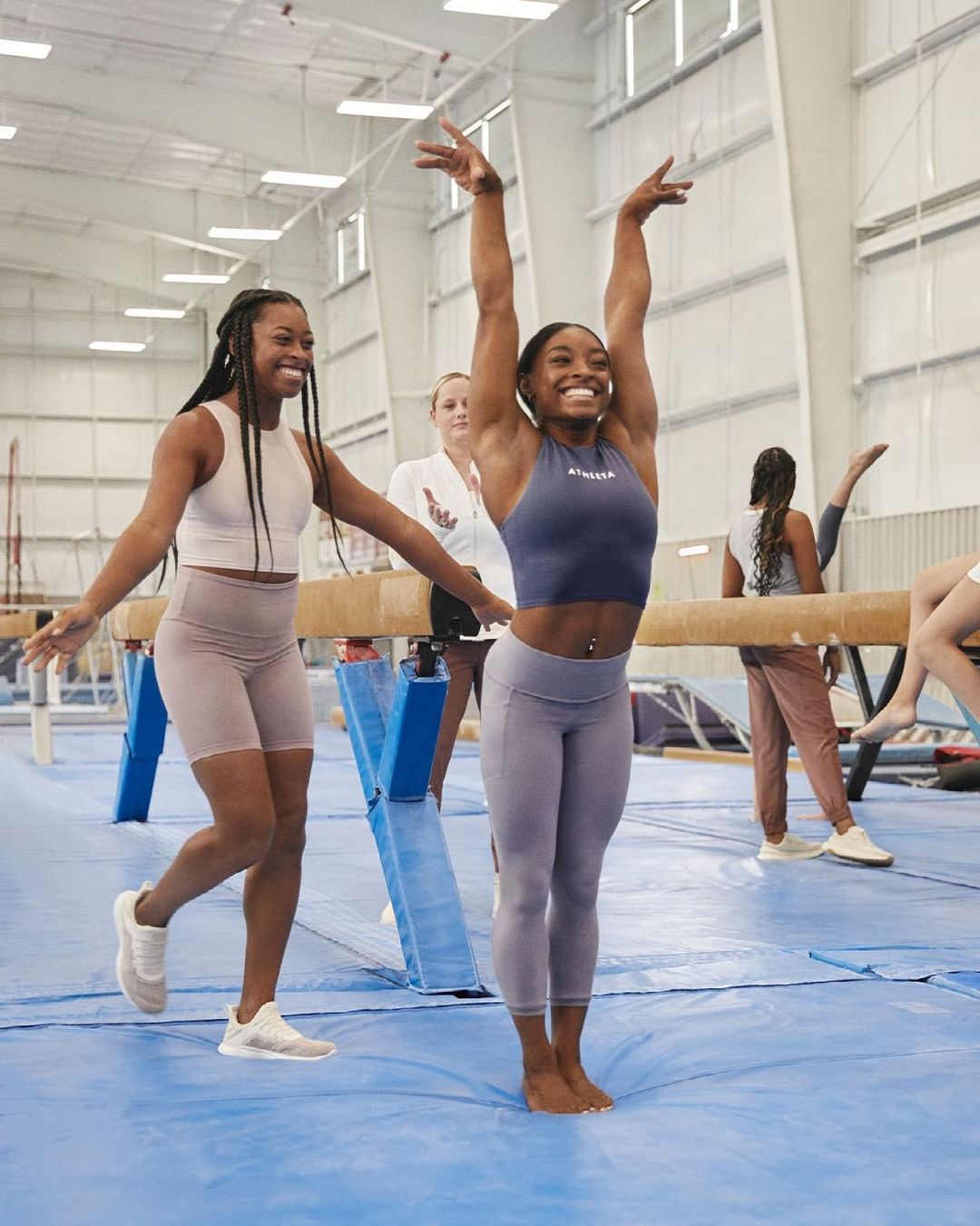 Biles, wearing a slate blue crop top and lighter blue leggings, poses in the gym like she is sticking her landing, with one girl smiling and walking behind her and several gymnasts training in the background.