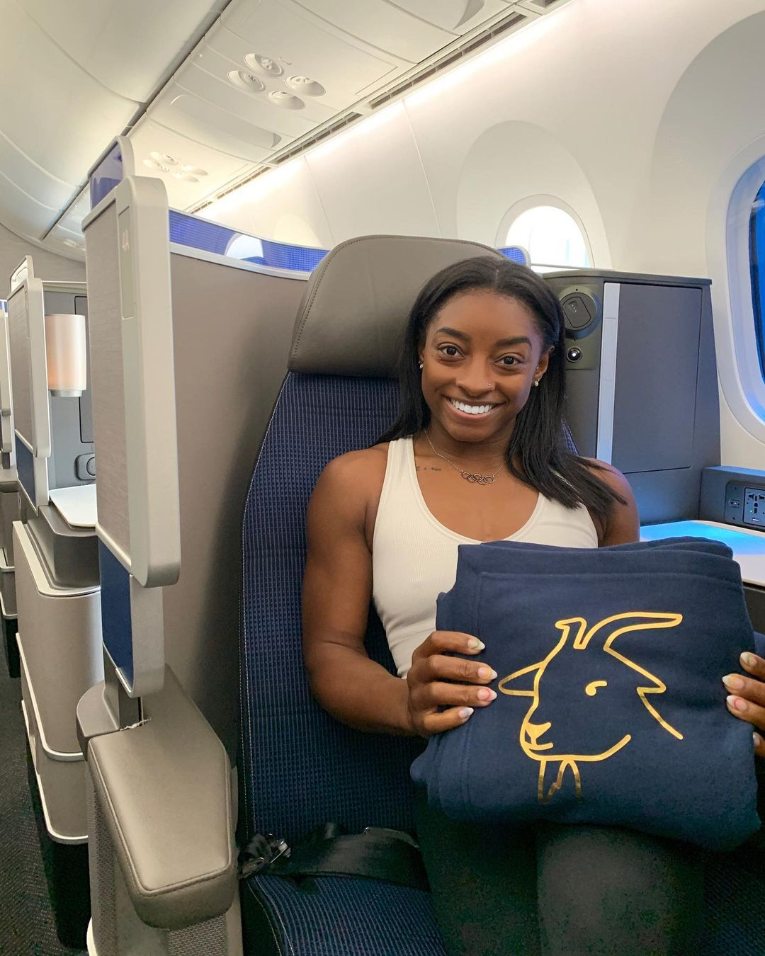 Simone Biles on the plane to Tokyo, holding a bag with a GOAT head emblem on it.