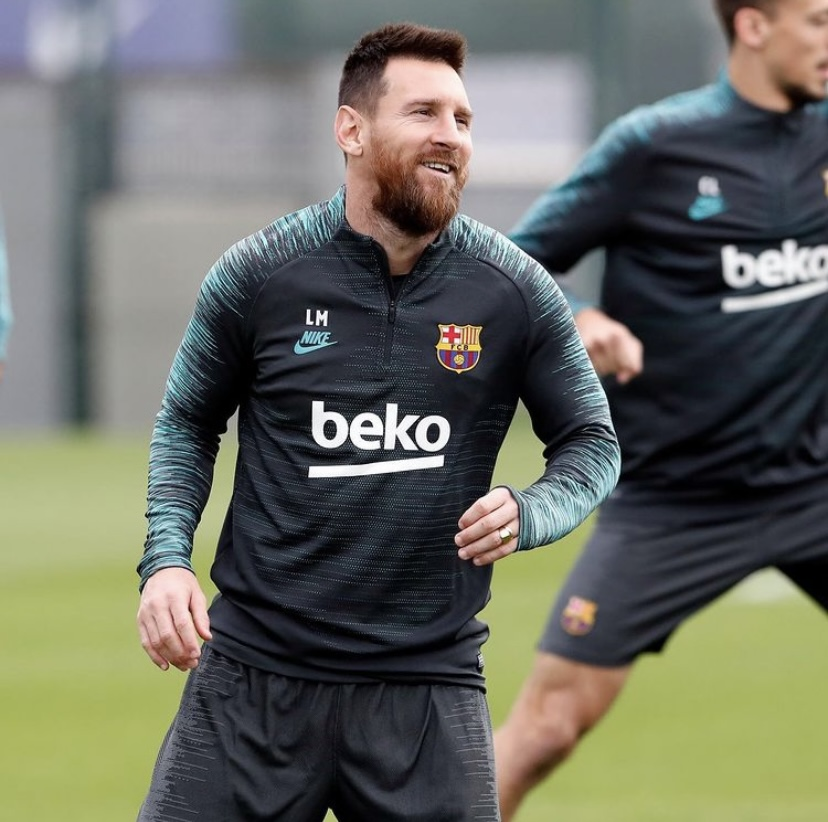 Messi smiling on the soccer field.