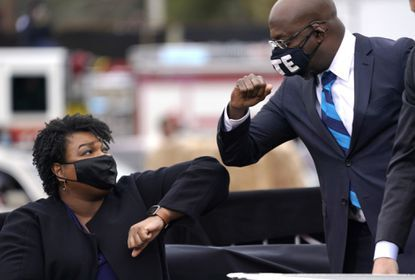 Stacey Abrams bumping elbows with U.S. Senator Raphael Warnock during a campaign rally for President Biden.