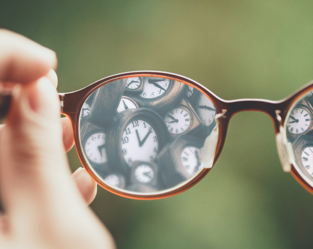 Reading glasses being held up by a hand, that feature a bunch of clocks on their lenses, some of which are blurry.