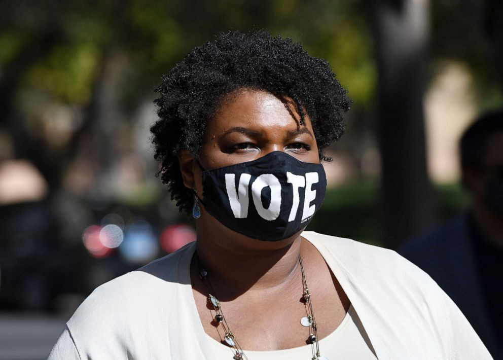 """Stacey Abrams wearing a mask with the word """"Vote"""" on it. Photo by Ethan Miller for Getty Images. Source: ABC News."""