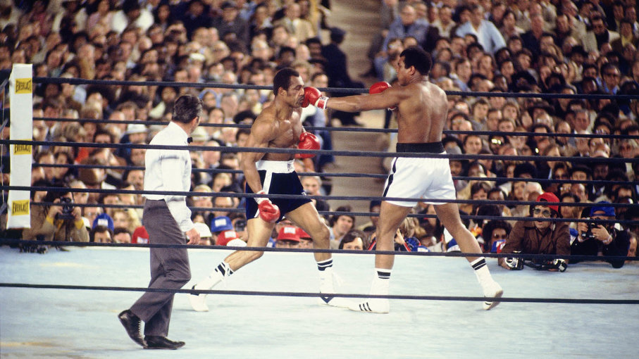 Muhammad Ali boxing in the ring and hitting his opponent