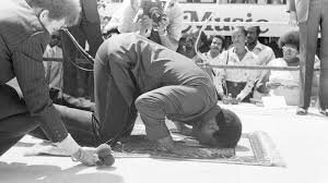 Muhammad Ali praying, kneeling on a mat with his head bowed down